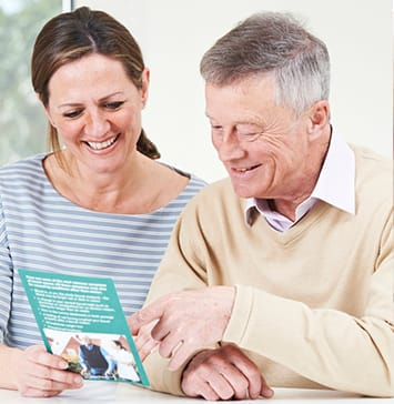 Senior Man With Daughter Looking At Brochure For Retirement